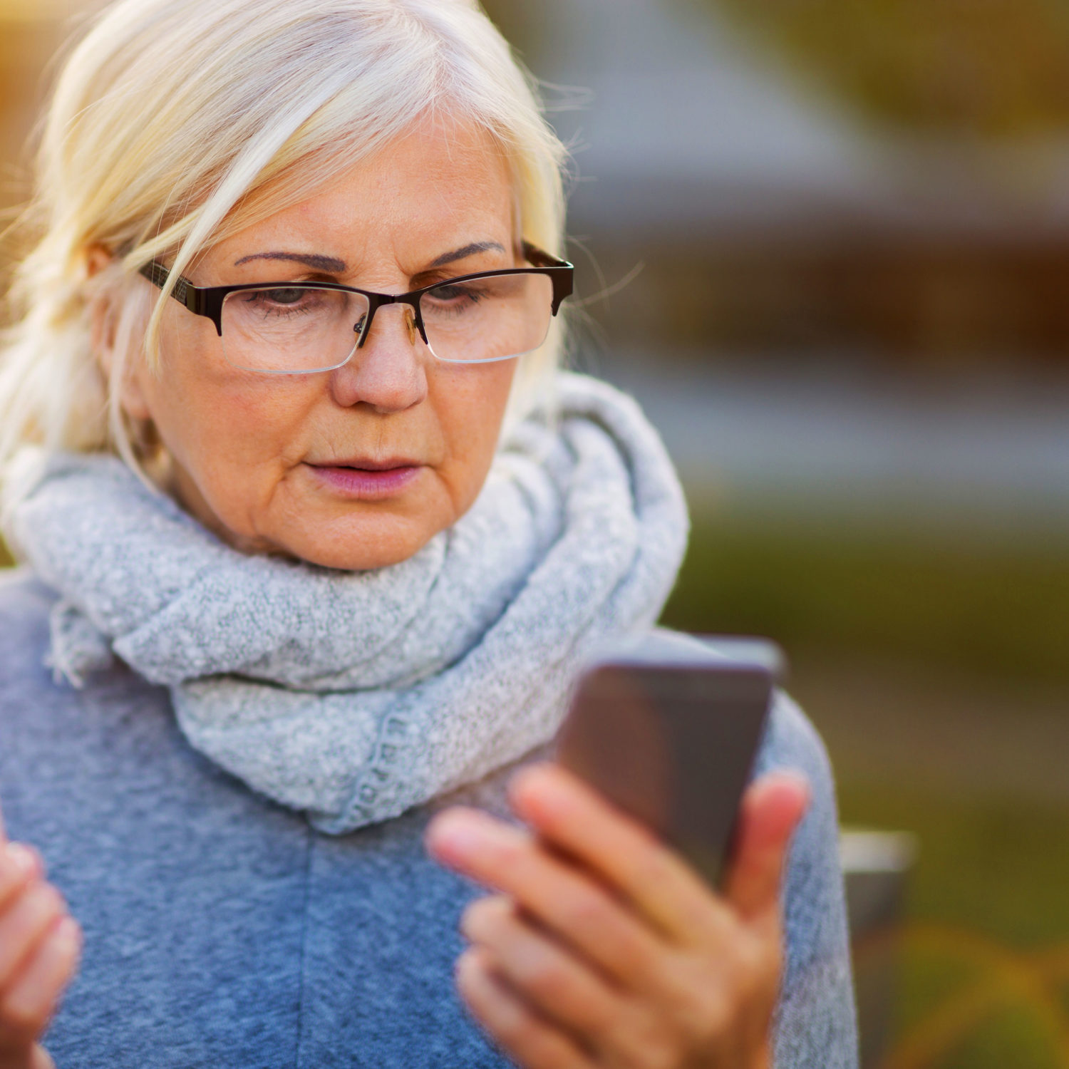 Older woman looking at her smartphone with a worried look